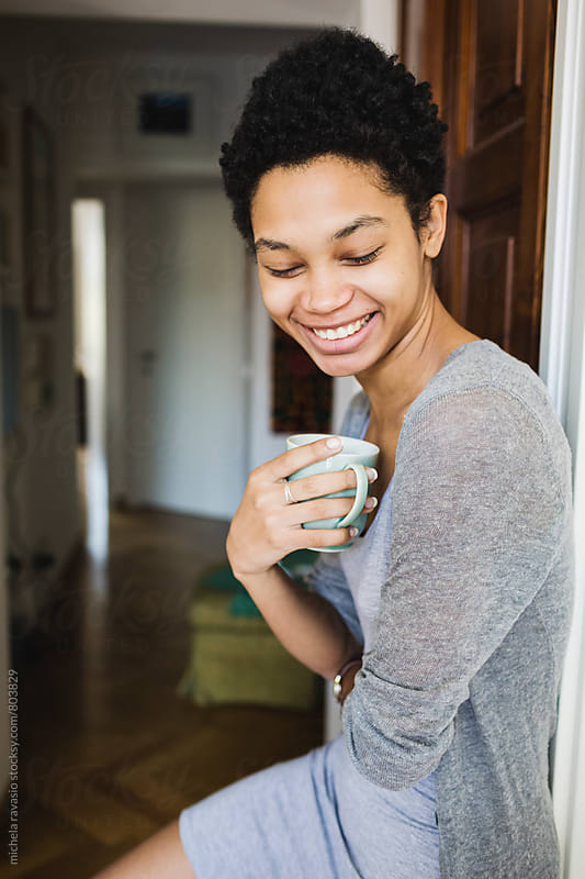 Smiling African woman holding a cup of coffee by michela ravasio for Stocksy United