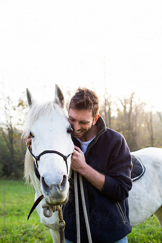 Happy man caressing his horse by michela ravasio for Stocksy United