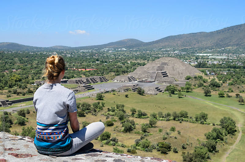Young woman sitting at the edge of pyramid overlooking Teotihuacan by Alice Nerr for Stocksy United