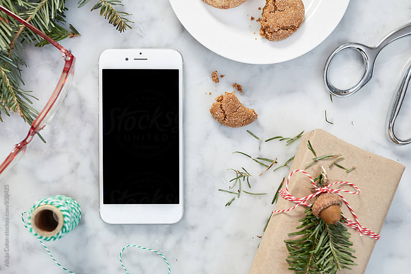 Christmas Chaos Surrounding a Phone by Alicja Colon for Stocksy United