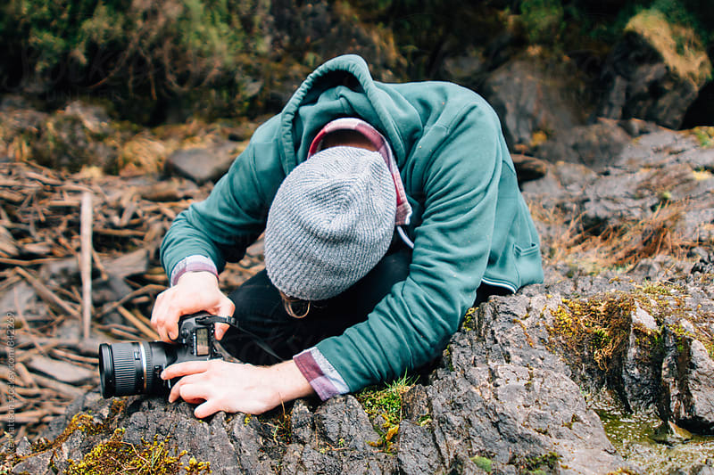 Young Man Positioning Digital SLR Camera On Rock To Take Outdoor Photographs by Luke Mattson for Stocksy United