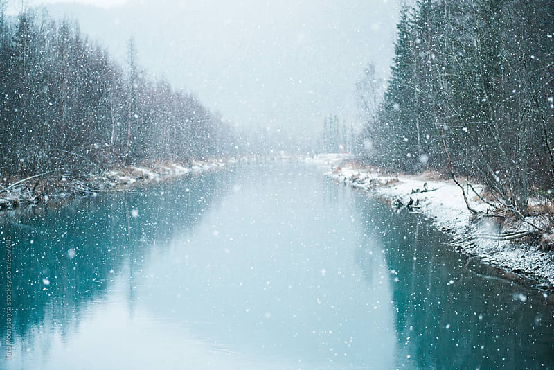 snow falling on a river by Tara Romasanta for Stocksy United