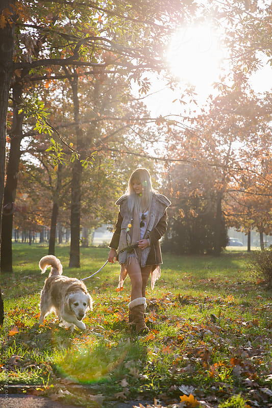 Beautiful blonde woman walking her dog in the park  by Jovo Jovanovic for Stocksy United