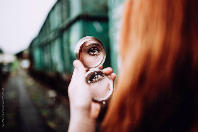 reflection of an eye in a mirror  by Thais Ramos Varela for Stocksy United