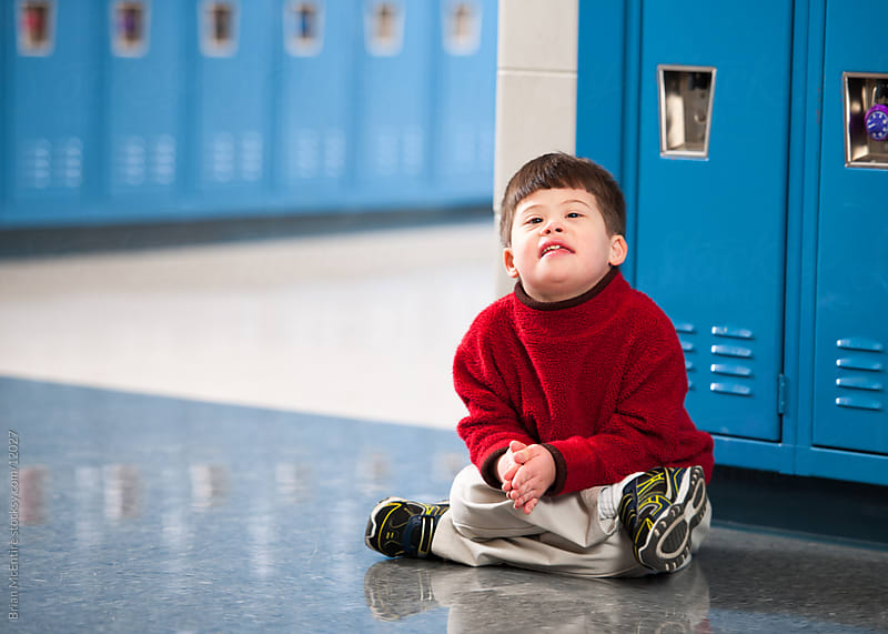 First Grade Boy with Down Syndrome Sitting By Lockers by Brian McEntire for Stocksy United