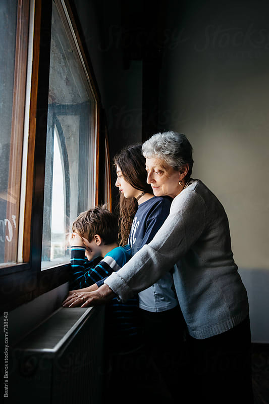 Two kids waiting by the window together with grandma by Beatrix Boros for Stocksy United