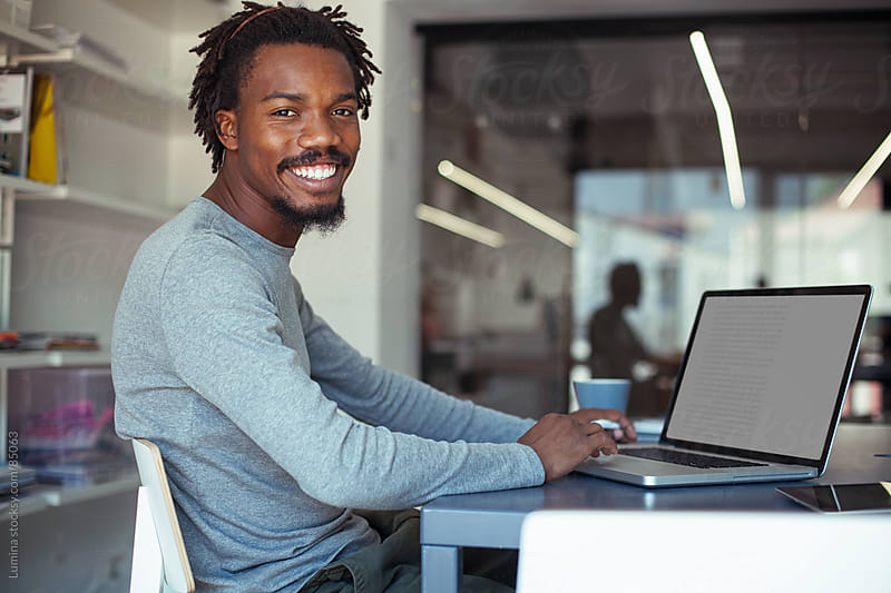 Smiling African Businessman at His Laptop by Lumina for Stocksy United