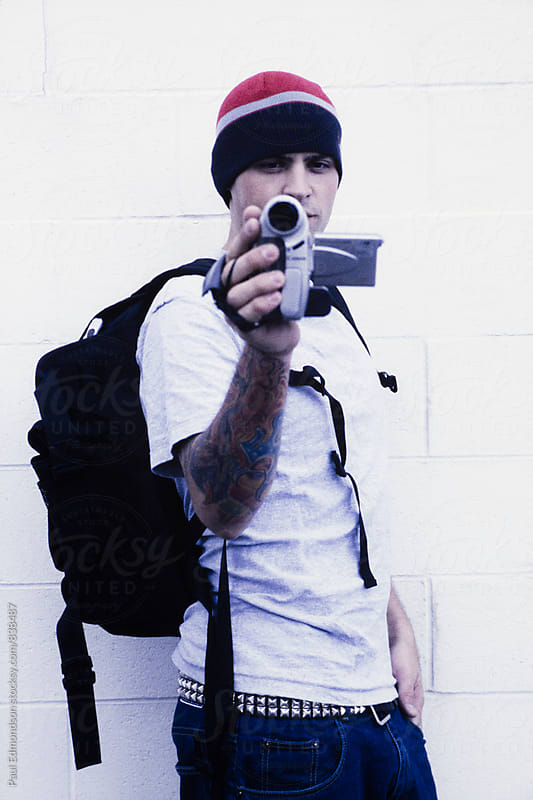 Young adult man with tattoos,  holding video camera by Paul Edmondson for Stocksy United