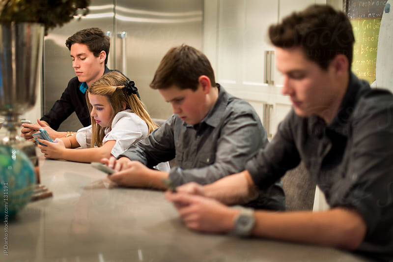 Family with Smart Phones At Kitchen Table by JP Danko for Stocksy United