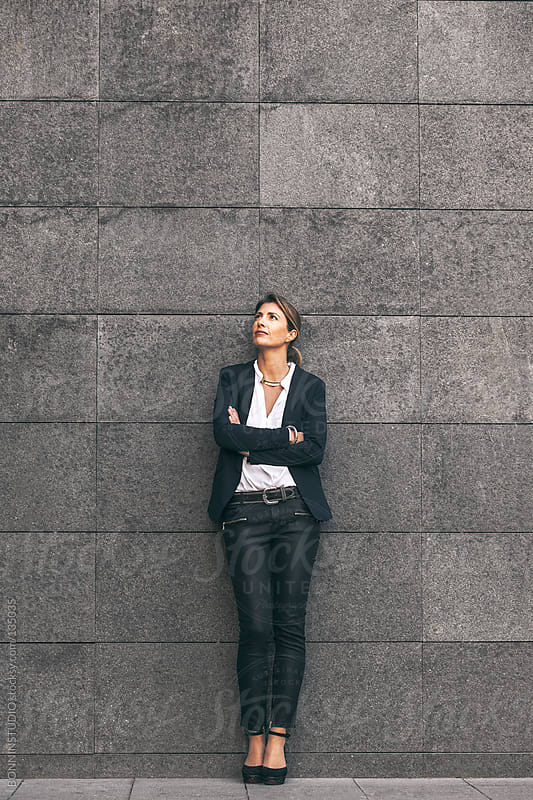 Business woman standing on urban wall. by BONNINSTUDIO for Stocksy United