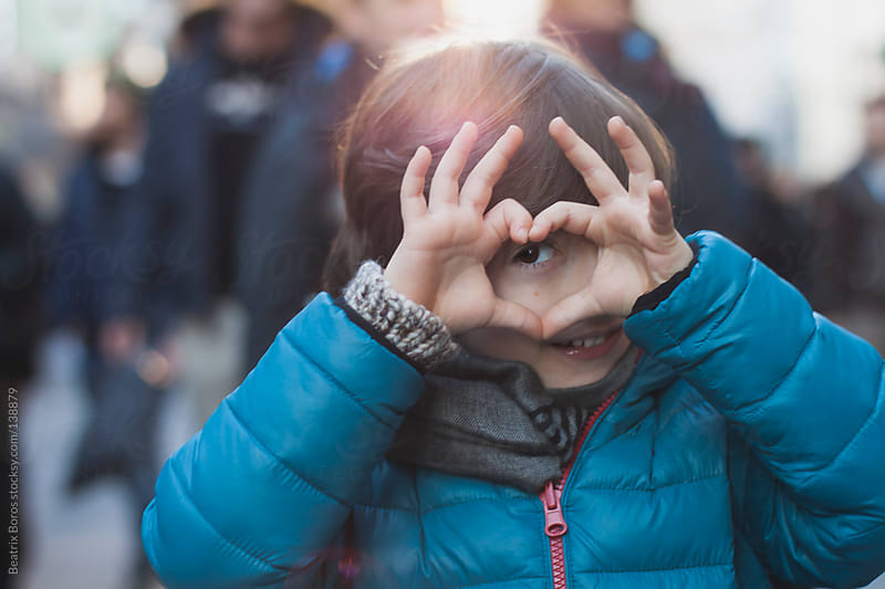 Boy shaping a heart with fingers in front of an eye by Beatrix Boros for Stocksy United