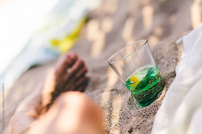 Summer cocktail in the sand - mint  and lemon by Borislav Zhuykov for Stocksy United