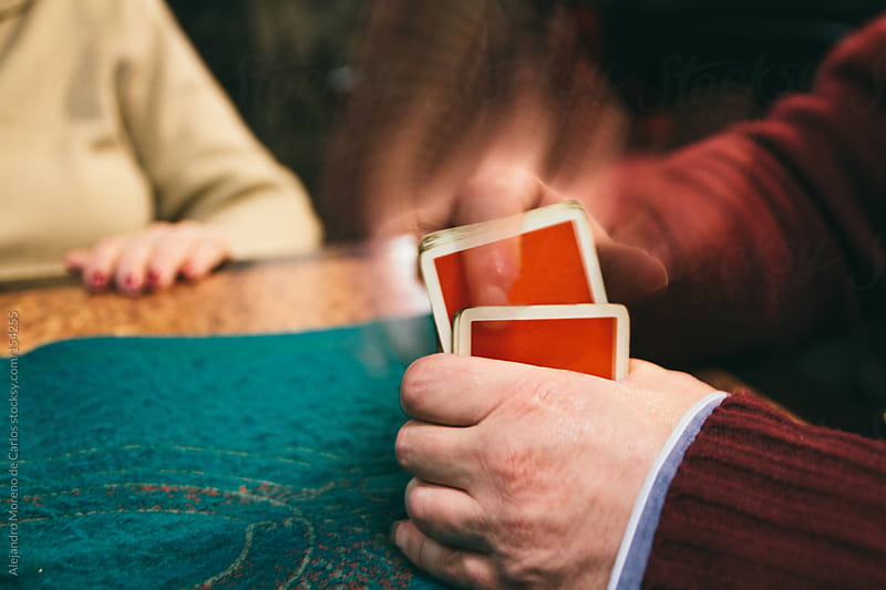Man shuffling deck of cards playing poker game by Alejandro Moreno de Carlos for Stocksy United