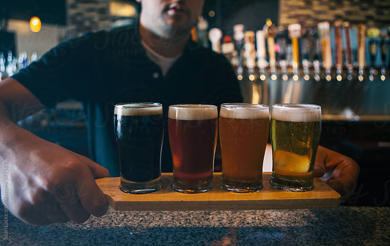 Bar: Bartender Serves Up Flight Of Different Beers by Sean Locke for Stocksy United