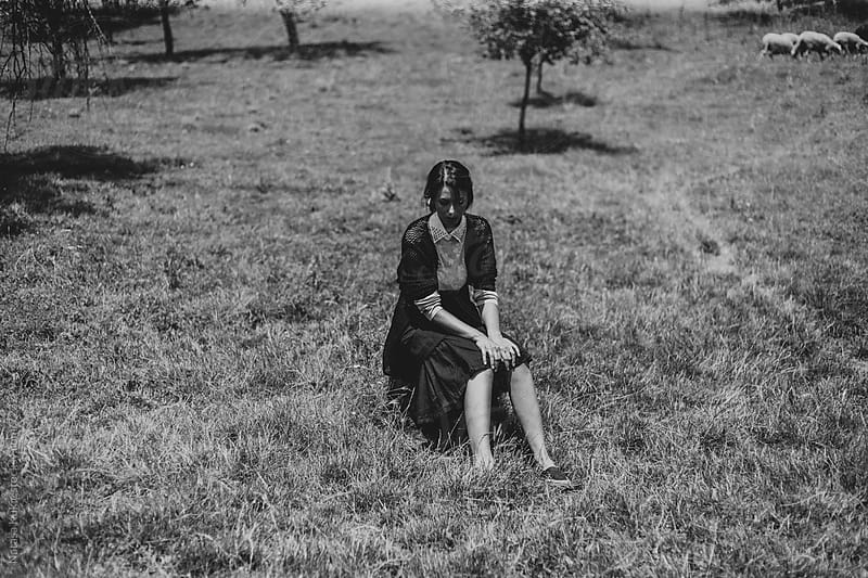 Young woman sitting alone in the middle of the meadow by Natasa Kukic for Stocksy United