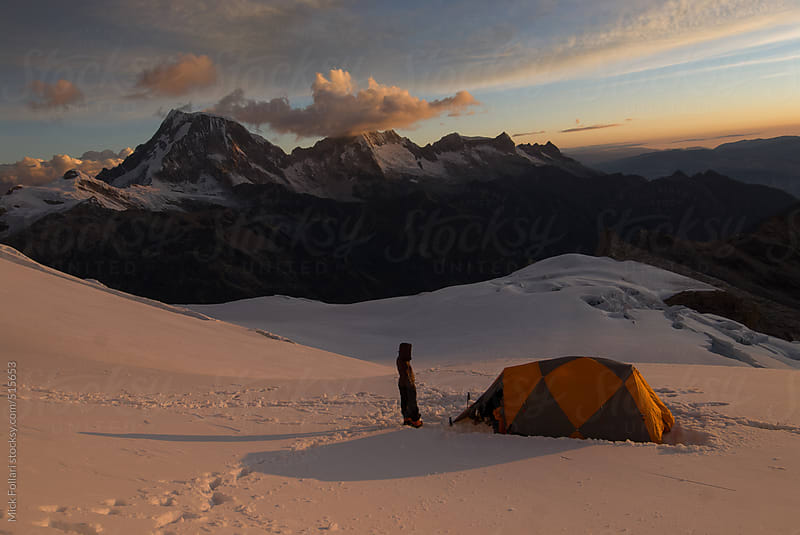Alpine climber and tent on high glacier at sunset with mountains behind. by Mick Follari for Stocksy United