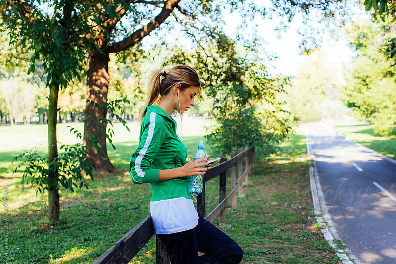 Female Runner Checking Phone in the Park by Mosuno for Stocksy United