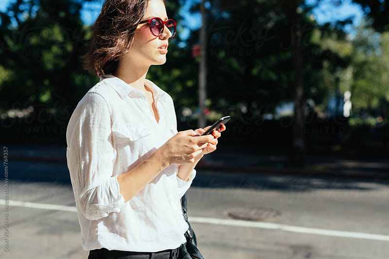 Woman walking in the city while holding a cell phone by Good Vibrations Images for Stocksy United