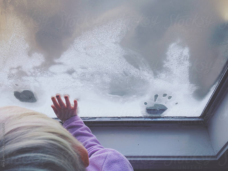 young girl making on handprints on frosty window by Jess Lewis for Stocksy United
