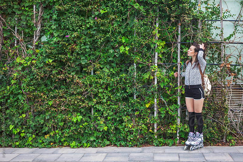 Young roller girl standing on ivy wall. by BONNINSTUDIO for Stocksy United