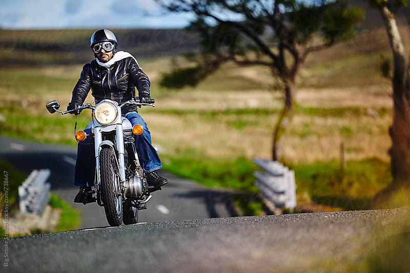 Caferacer biker going on a rural road by Big Smoke Studio for Stocksy United