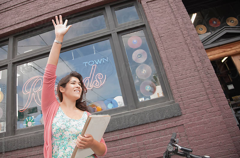 Young woman hailing for taxi in front of record shop by Andersen Ross Photography for Stocksy United