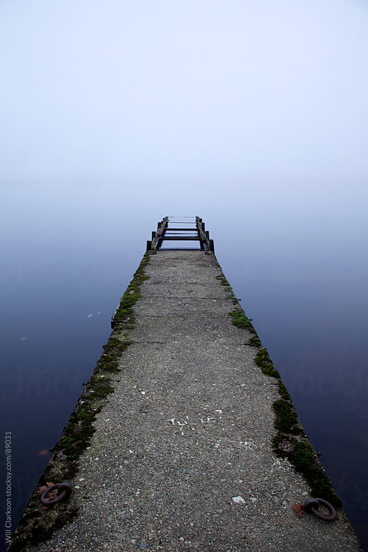 Pier leading out into a misty lake by Will Clarkson for Stocksy United