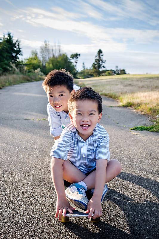 Happy Asian kids having fun on a skateboard outdoor in a park by Suprijono Suharjoto for Stocksy United
