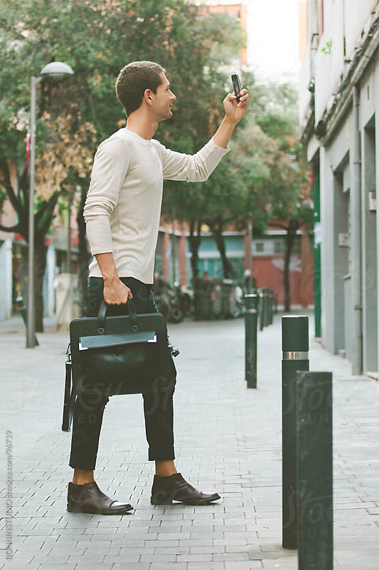Casual businessman taking photos with phone on the street. by BONNINSTUDIO for Stocksy United
