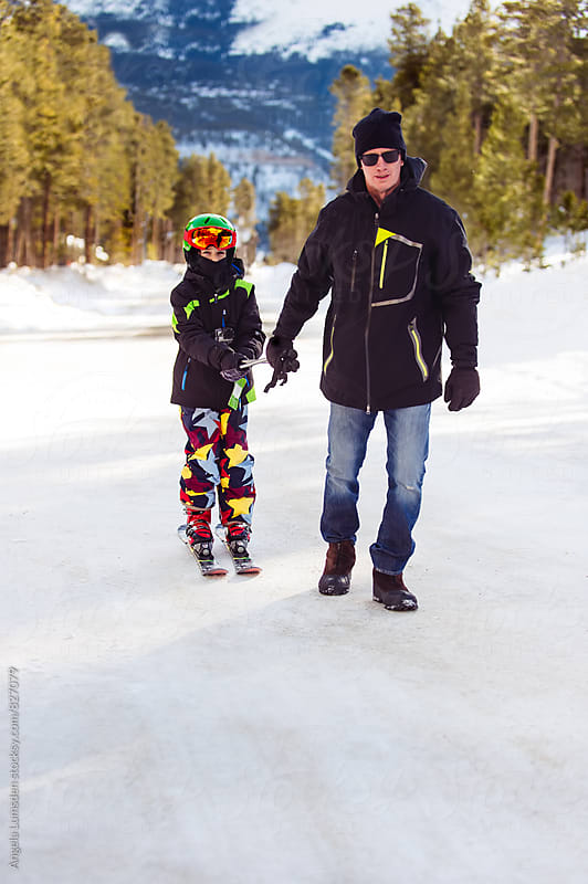 Father towing his son on skis on a snow-covered road by Angela Lumsden for Stocksy United