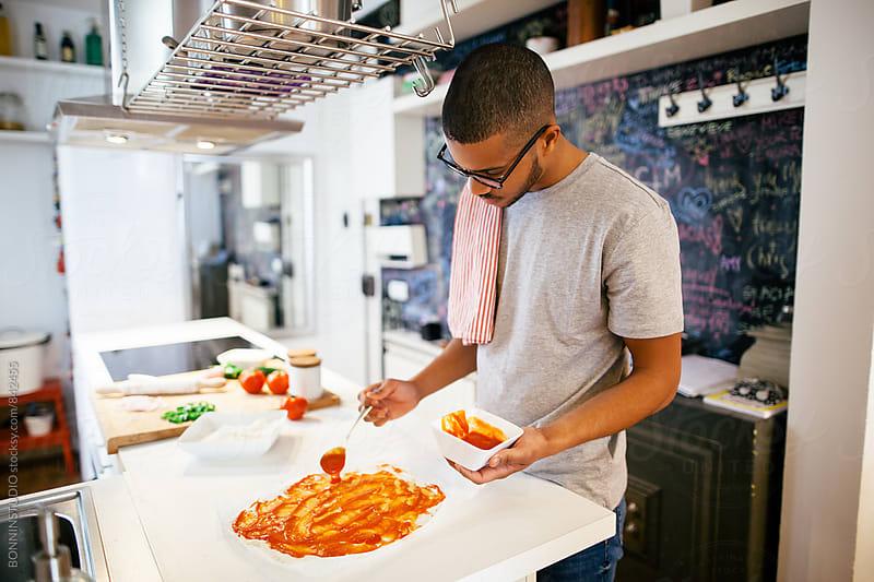 Man preparing a handmade Italian pizza in the kitchen. by BONNINSTUDIO for Stocksy United