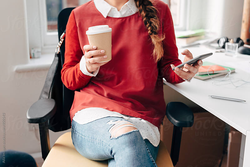 Businesswoman using smart phone drinking coffee at work on break by Aila Images for Stocksy United