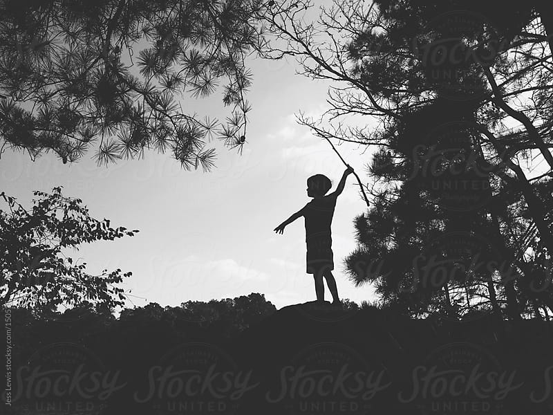 silhouette of boy in nature holding stick by Jess Lewis for Stocksy United