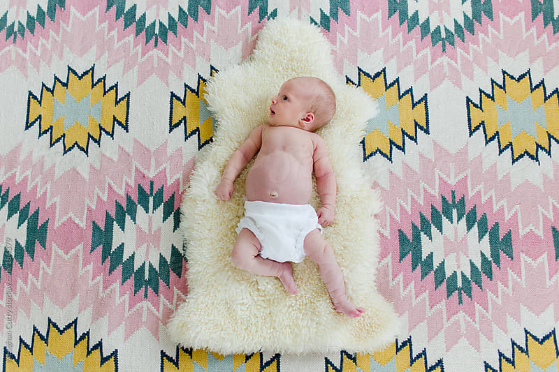 newborn laying on a sheepskin and a patterned rug by Meaghan Curry for Stocksy United