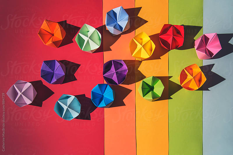 Rainbow fortune tellers on multi-coloured background... by Catherine MacBride for Stocksy United