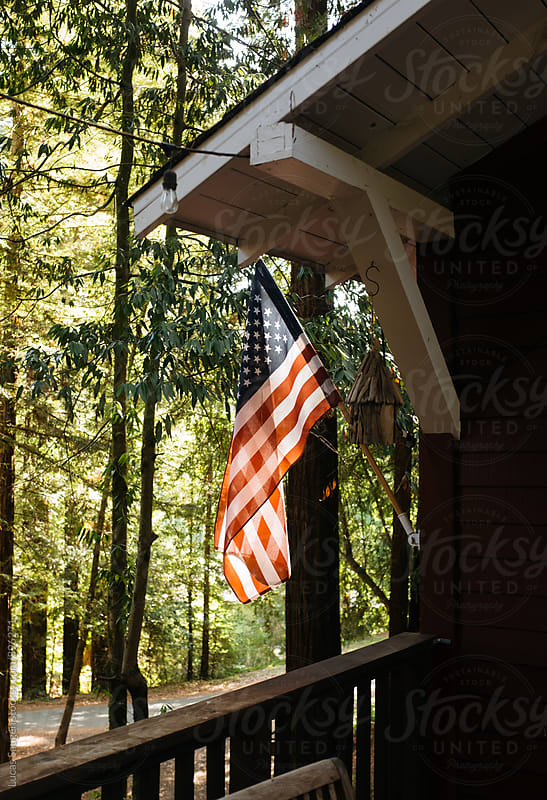 American flag hanging outside a cute woodsy cabin. by Lucas Saugen for Stocksy United