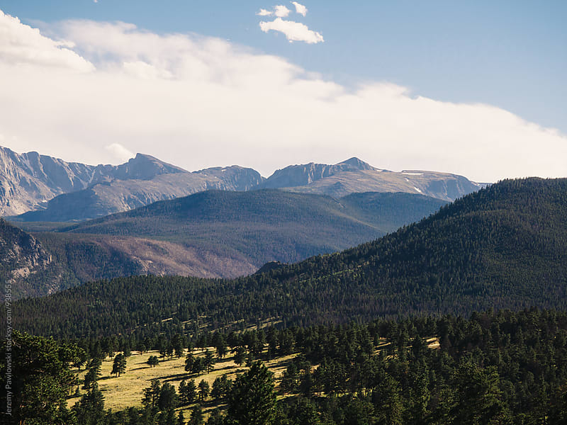 Colorado landscape with trees, mountains, clouds and sky by Jeremy Pawlowski for Stocksy United