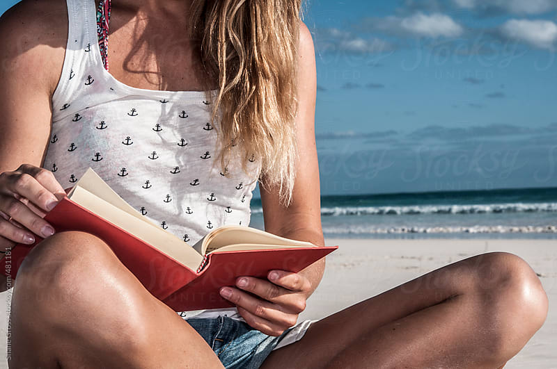 Sitting and Reading on the Beach by Shane Gross for Stocksy United
