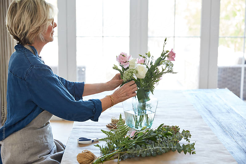 Senior Woman Arranging Flowers In Vase On Table Stocksy United