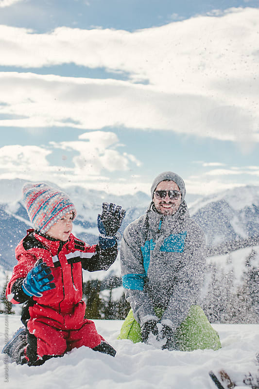 father and son having fun outdoors and playing in the snow by Leander Nardin for Stocksy United
