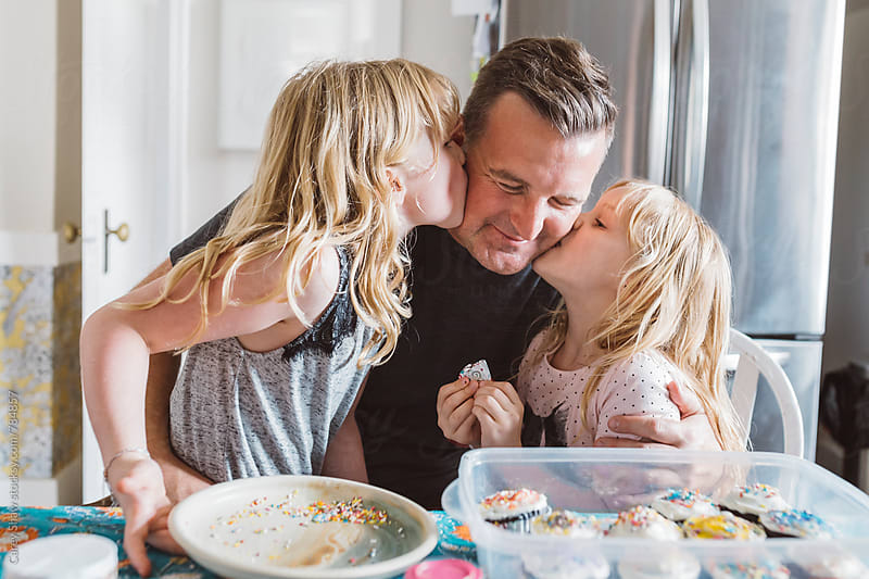 Daughters giving father a kiss by Carey Shaw for Stocksy United