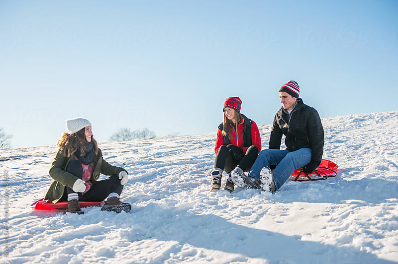 Friends talking during break from sledding on crisp winter day by Brian McEntire for Stocksy United