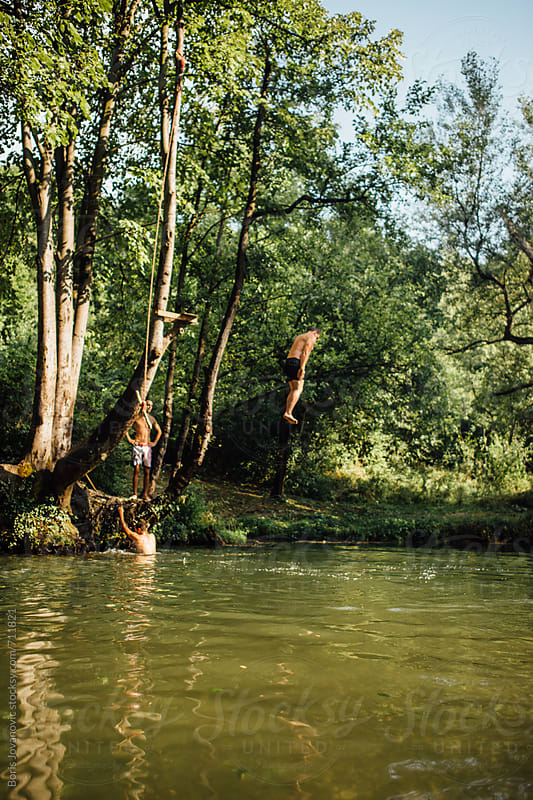 Man jumping in the river  by Boris Jovanovic for Stocksy United
