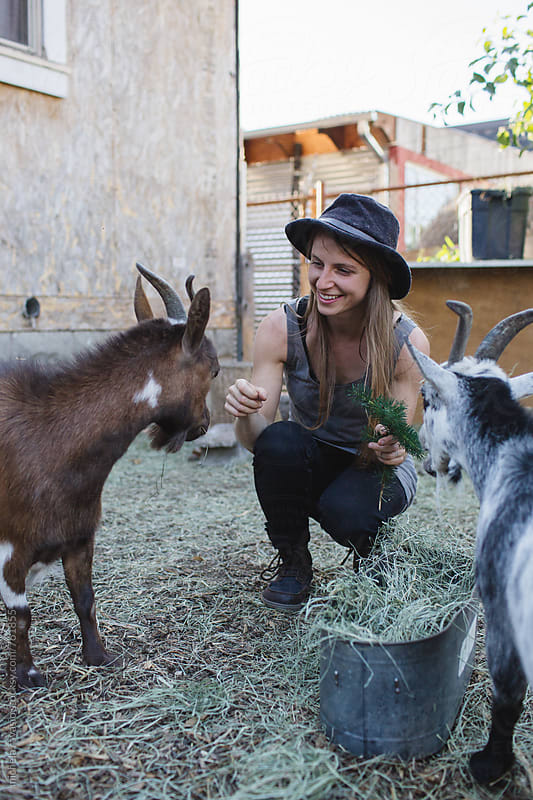 Girl feeds her goats by michela ravasio for Stocksy United