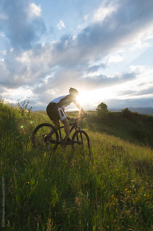 Cyclist man riding  downhill above sunset valley by RG&B Images for Stocksy United