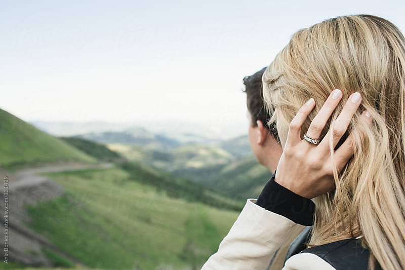 A blonde woman and her fiancé looking out into a valley with a diamond ring on her finger by Ania Boniecka for Stocksy United