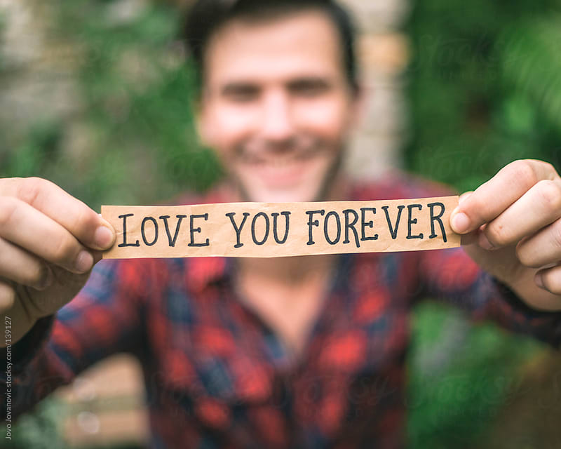 Young man in love holding love you forever message.  by Jovo Jovanovic for Stocksy United
