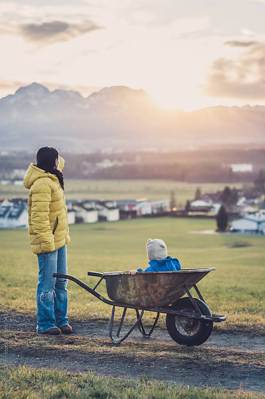 mother and son watching a beautiful sunset by Leander Nardin for Stocksy United