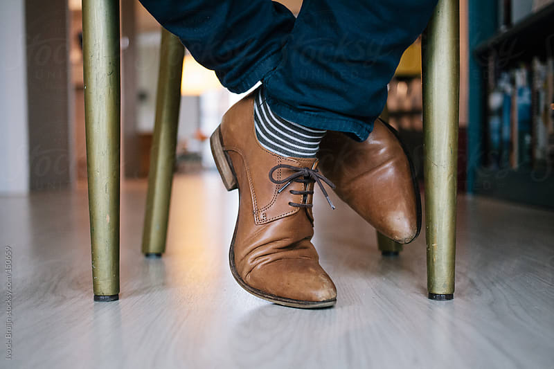 Shoes of someone sitting behind his desk at home by Ivo de Bruijn for Stocksy United