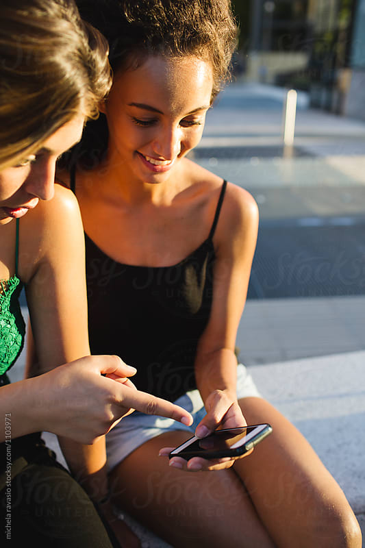 Couple of friends looking at mobile devices